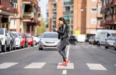 Pietonii, amendați dacă traversează strada cu ochii în telefon!